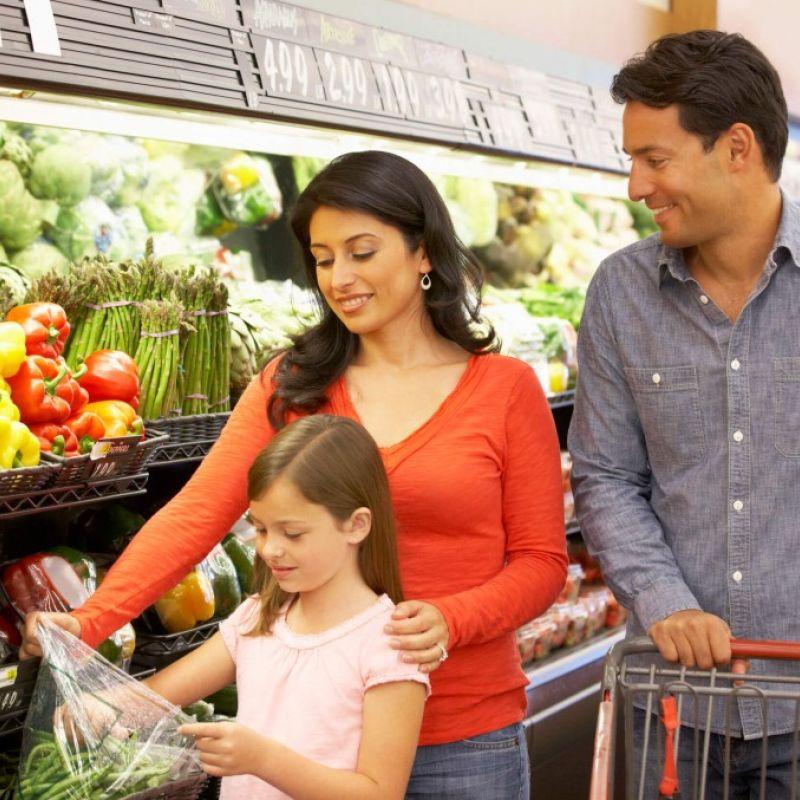 Parents and kid choosing vegetables