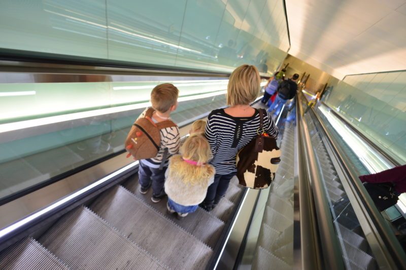 mother traveling with three kids