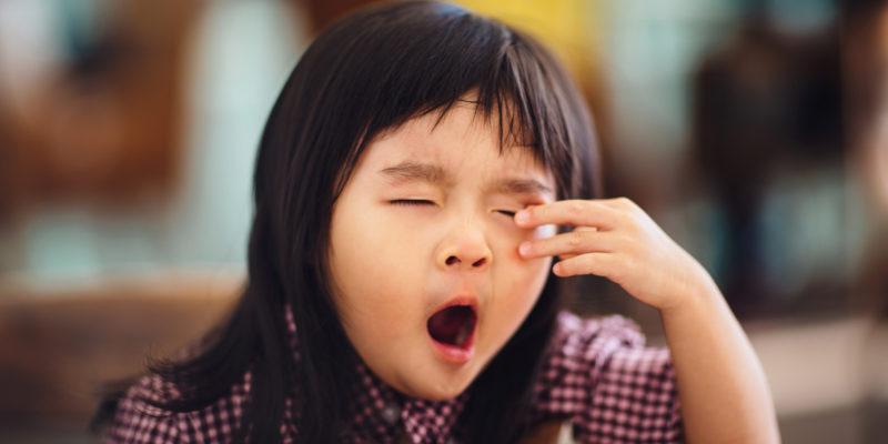 Toddler girl yawning and rubbing eyes