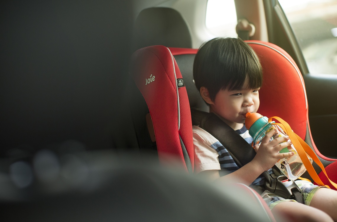 Little boy drinking in a car seat