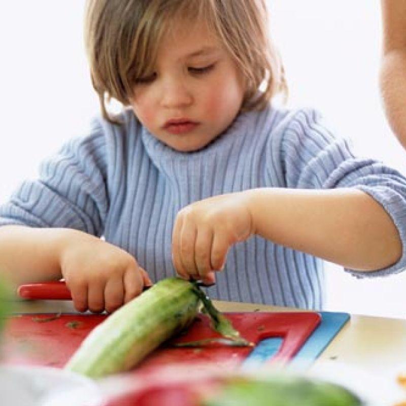 Boy cutting cucumber