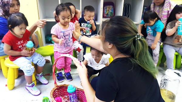 Soraya interacting with her teacher at the Toddler Class in KDSF.