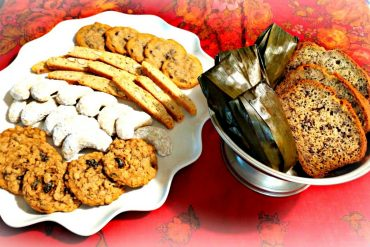 In the platter from the top down: chocolate chip cookies, almond biscotti, walnut crescents, and oatmeal cookies. In the bowl: banana bread and steamed sticky rice with bananas in banana leaves.