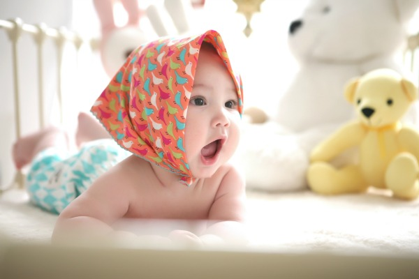 Baby girl on bed. Mummy Hacks to Make Diaper Changing