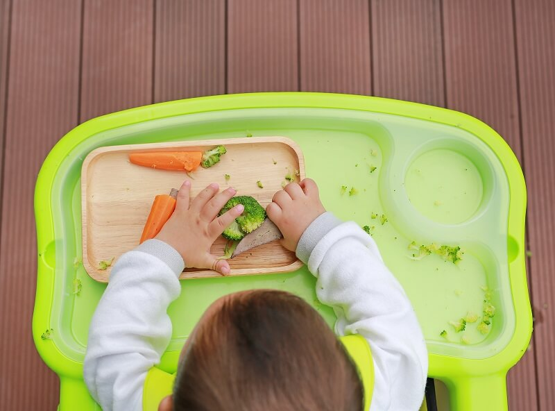 Baby sitting on high chair and grab solids foods during baby led weaning.