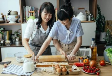 A daughter is helping her mother to knead the dough.