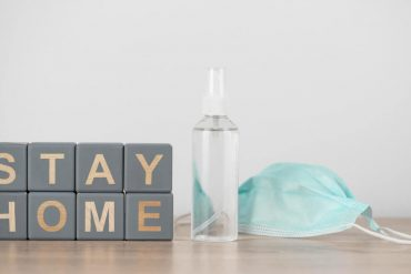 Sanitizer and face mask are placed next to the wooden cubes stating 'stay home'.