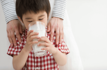 A cute Asian toddler is drinking a big glass of organic milk.