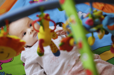 A four-month-old baby is lying down with a hanging toy on top of her.