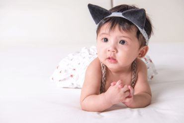 A cute six-month-old is posing with a cat hairband.