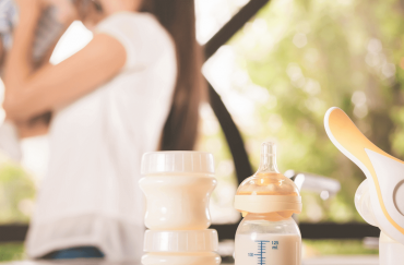 A mother is kissing her baby while showing the wireless breast pump.