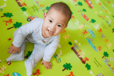 A seven-month-old baby is sitting on a play mat happily.