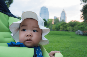A 8-month-old-baby is sitting in a stroller.
