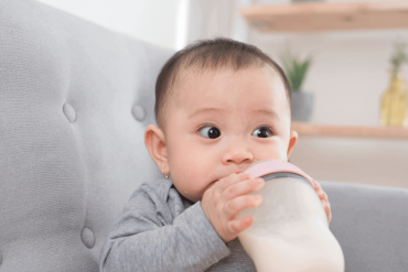 A 9 -month-old is drinking milk from a bottle.