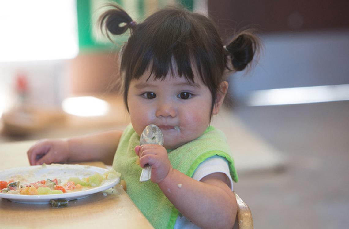 Little girl feeding herself