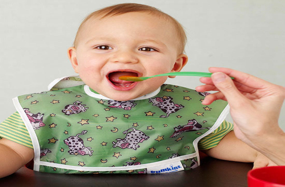 happy baby eating and wearing green bib