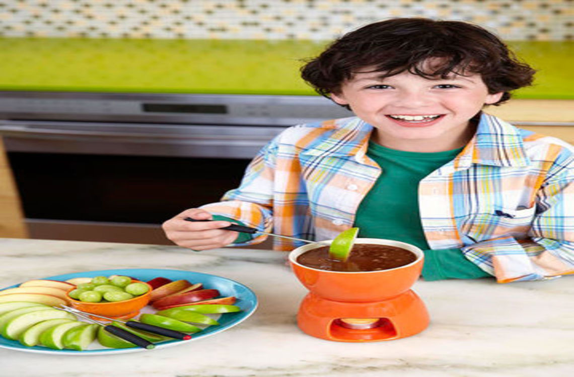 a boy dipping an apple into a caramel fondue