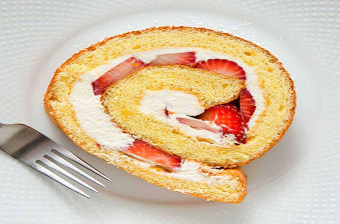 A slice of rolled strawberry roulade