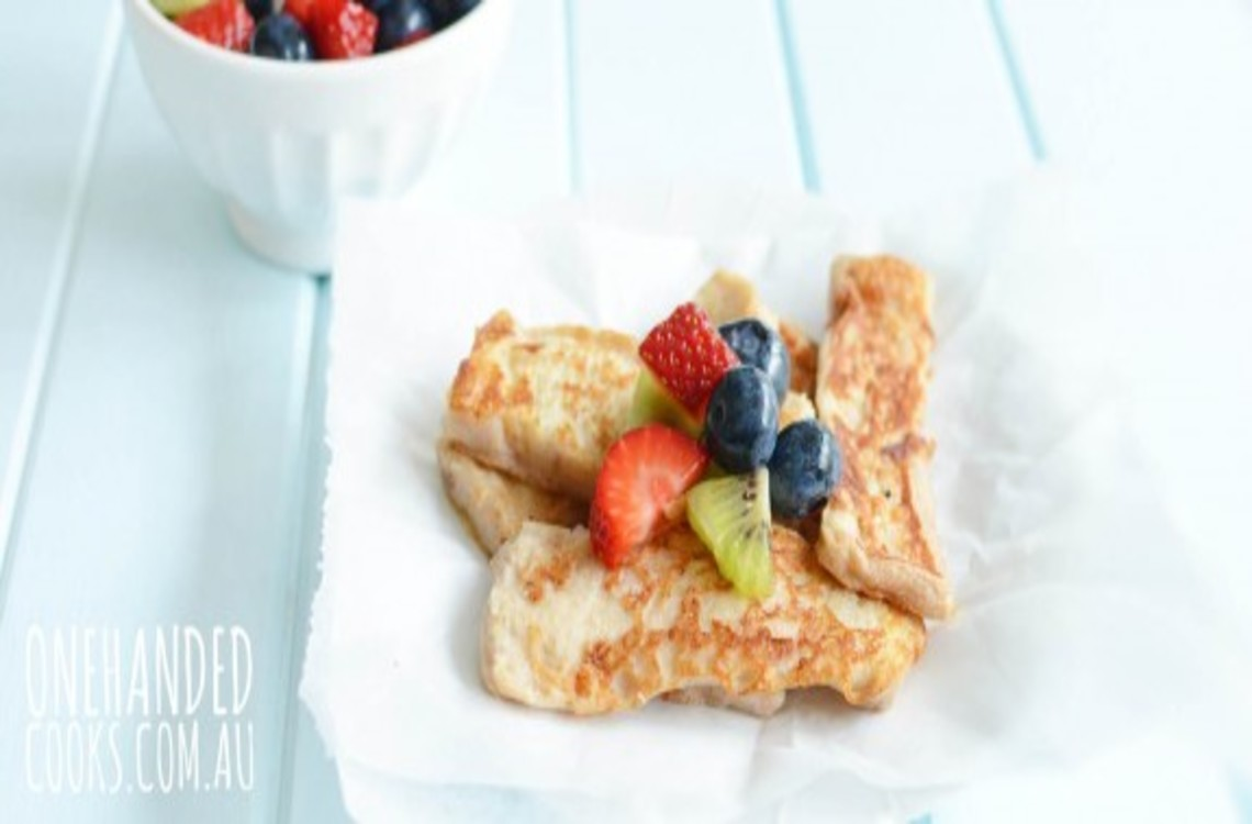 a plate of banana toast with berries on top